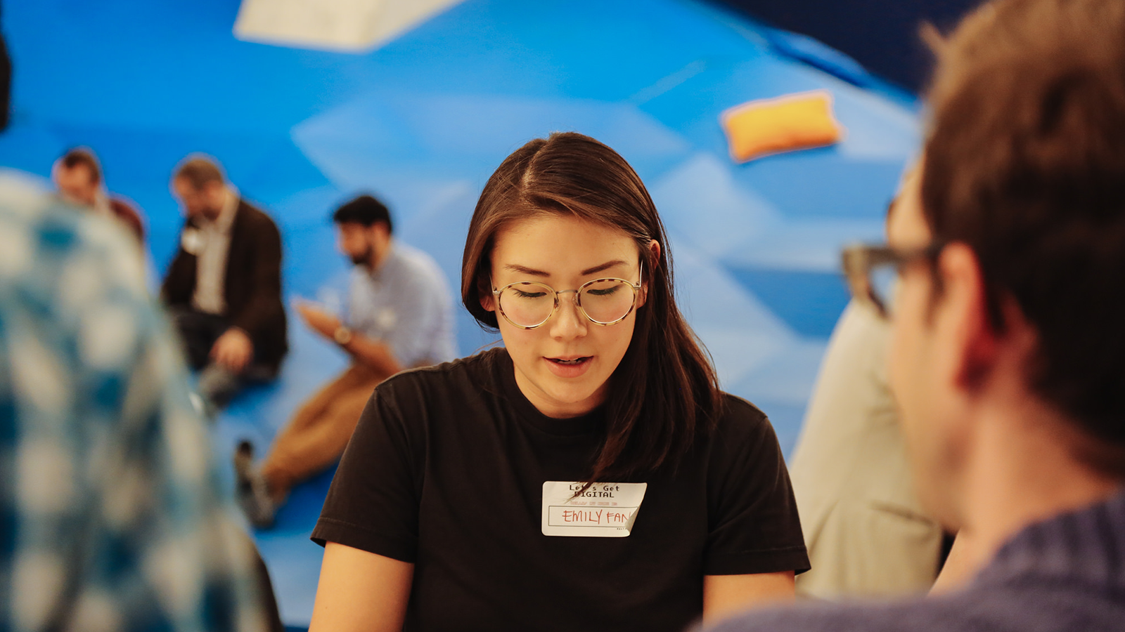 Woman with glasses, brown shirt, and name tag at gathering looking down.
