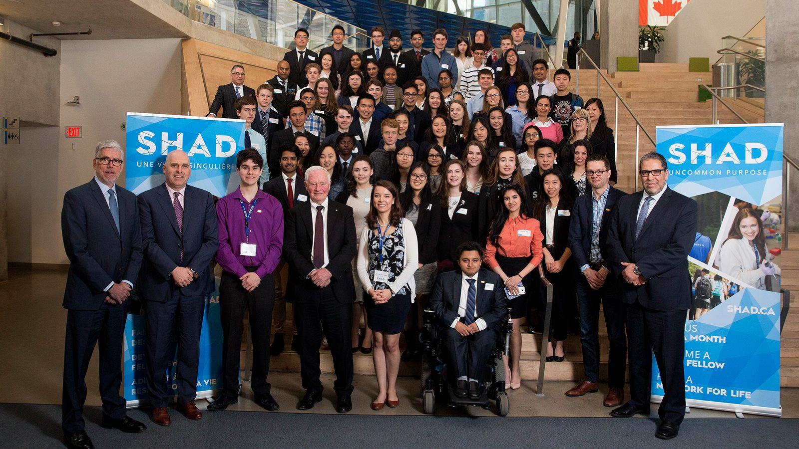 Group photo of executives and students together on stairs next to SHAD banners.