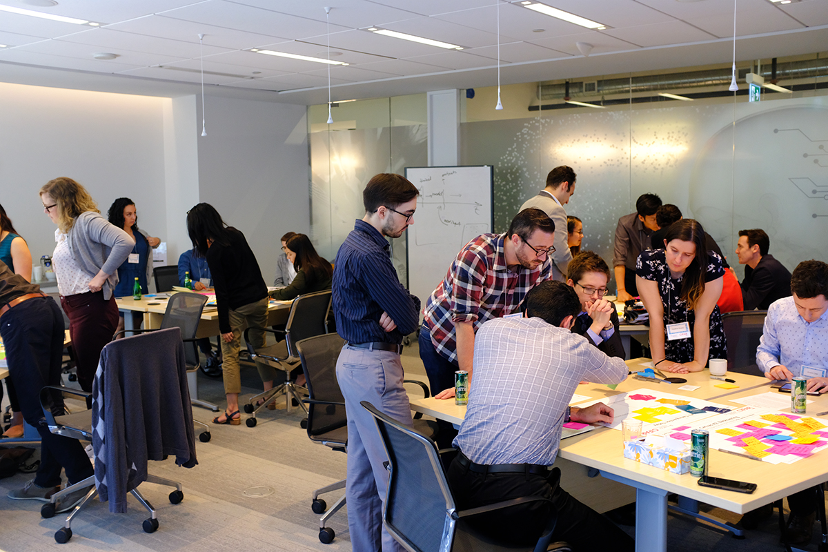 Photo of people sitting and standing collaborating at desks.