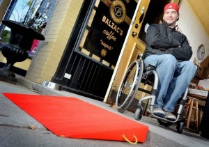 Photo of man in wheelchair next to red wheelchair ramp.