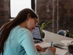Photo of woman writing at desk.